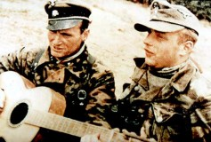 "During a break in the fighting, SS-Untersturmführer Franz-Josef ""Franzl"" Kneipp (Signal officer of III.Bataillon / SS-Panzergrenadier-Regiment 25 / 12.SS-Panzer-Division ""Hitlerjugend"") plays his guitar in the trenches with the battalion adjutant, SS-Untersturmführer Kurt Bergmann, and just out of sight to the left is Battalion Commander SS-Obersturmbannfuhrer Karl-Heinz Milius."