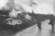 An American soldier escorts a German crewman from his wrecked Panther tank during the Battle of Elsenborn Ridge.