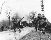 German troops advancing past abandoned American equipment.