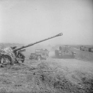 A Cromwell tank and Willys MB jeep passing an abandoned German 88 mm (3.46 in) PaK 43 anti-tank gun during Totalize.