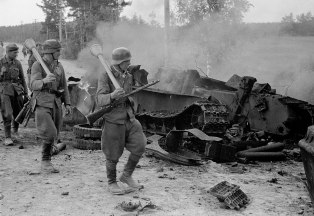 Finnish troops passing by the remains of a destroyed Soviet T-34 at the battle of Tali-Ihantala.