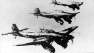 "Formation of Ju 87A dive-bombers, with the A's characteristic large wheel ""trousers"", each having one transverse bracing strut."