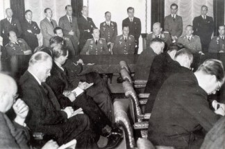 "Berlin, 20 December 1939 – a press conference organized by Dr. Otto Dietrich of Goebbels' Propaganda Ministry on the occasion of a great victory over British bombers achieved by German fighters over the Wilhelmshaven area on 18 December 1939. Seated at the table are pilots who fought in this battle. On the extreme right is Oberleutnant Wolfgang Falck of I.Gruppe / Zerstörergeschwader 76 (ZG 76); third from the right is Oberstleutnant Carl Schumacher, Gruppenkommandeur Jagdgeschwader 1 (JG 1); between Falck and Schumacher is Dr. Otto Dietrich in SS-Gruppenführer uniform; and third from the left is Oberleutnant Johannes Steinhoff of 10.(N)Staffel / III.Gruppe / Jagdgeschwader 26 (JG 26) ""Schlageter"". Both Oberleutnants (Falck and Steinhoff) claimed two victories in the battle, while the commander of the whole formation (Schumacher) claimed one."
