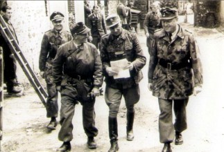 Three senior German commanders in the Battle against Allied troops in St.-Lô area, Normandy, 16 July 1944. From left to right: General der Fallschirmtruppe Eugen Meindl (Kommandierender General II. Fallschirmkorps), SS-Obergruppenführer und General der Waffen-SS Paul Hausser (Oberbefehlshaber 7. Armee), and Generalleutnant Dipl.Ing. Richard Schimpf (Kommandeur 3. Fallschirmjäger-Division). Behind Schimpf is SS-Hauptsturmführer Karl-Heinz Boska (Adjutant Oberbefehlshaber 7. Armee). In this meeting Meindl told his commander, Hausser, that the German defense position at St.-Lô was untenable any longer due to the superiority of the Allied forces on land and in the air.
