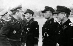 """The photo is taken on May 19, 1944 at Cholm from an awards ceremony for the SS-Panzer-Regiment 5 of 5. SS-Panzer-Division """"Wiking"""". From left to right: SS-Sturmbannführer Paul Kümmel (Kommandeur I.Abteilung / SS-Panzer-Regiment 5 """"Wiking""""), SS-Standartenführer Johannes Mühlenkamp (Kommandeur SS-Panzer-Regiment 5 """"Wiking""""), SS-Obersturmführer Kurt Schumacher (Führer 3.Kompanie / I.Abteilung / SS-Panzer-Regiment 5 """"Wiking""""), SS-Untersturmführer der Reserve Paul Senghas (Zugführer in 1.Kompanie / I.Abteilung / SS-Panzer-Regiment 5 """"Wiking""""), and unidentified SS-Oberscharführer (possibly also from I.Abteilung / SS-Panzer-Regiment 5 """"Wiking"""")."""