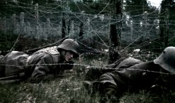 Finnish soldiers advancing under barbed-wire obstacles on the Hanko front.