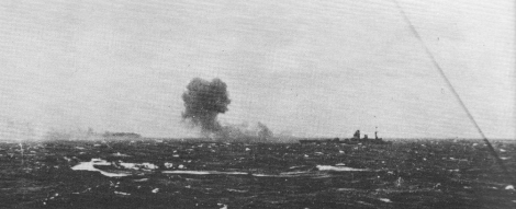 Rodney firing on Bismarck, which can be seen burning in the distance.