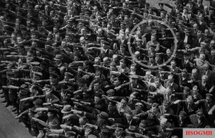 A lone man with his arms folded as hundreds around him salute at the launch of the Horst Wessel, 1936.