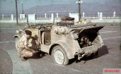 A German driver operating a jack in changing a flat tire on a Kübelwagen Typ 82 with engine visible in Sicily, Italy, 1943.