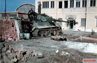 """A rare color photo, taken in March-April 1944, showing a Panzerkampfwagen VI Tiger from schwere Panzer-Abteilung 508 undergoing repairs in the Workshop Company's (Werkstattkompanie) position in front of the buildings of the former """"Arco"""" bomb factory near the Forte Tiburtino, Rome (Italy). The camouflage finish and crosses are just visible on the Tiger. The exhaust boxes and cover plates have been removed. The cover plates are lying on the ground to the right of the tank."""
