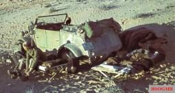 Somewhere in the North African desert: DAK (Deutsches Afrikakorps) soldier get ready to wear his shoes in a feldbett (field cot) near his Kübelwagen (number plate WH, Wehrmacht Heer, 936769) while his friend still wrapped in blanket.