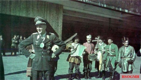 """Send-off celebration for Luftwaffe ace Major Adolf Dickfeld as he leaves II.Gruppe / Jagdgeschwader 11 (JG 11) to take up his new post as a """"General für Führernachwuchs im Reichs-Luftfahrt-Ministerium und Reichs-Inspekteur der Flieger- Hitlerjugend"""" (General of recruitment of the Luftwaffe in the Reich Air Ministry and Reich inspector of the Hitler Youth Aviation). The photo was taken at Jever airfield, Niedersachsen (Germany), 31 May 1943, and it also shows a Cossack band taken from Caucasus!"""