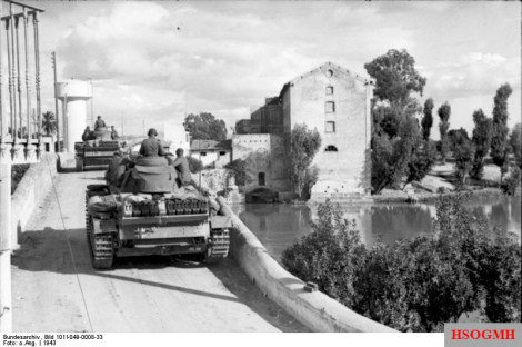 German Panzer Mk III tanks advance through a Tunisian town.