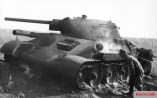 A German soldier inspects a T-34 tank knocked out at Pokrovka that is still smoldering. Pokrovka is 40 kilometres (25 mi) southwest of Prokhorovka.
