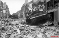 Knocked out German tanks on the main street of Villers-Bocage. Historian Henri Marie claims that the Tiger in the foreground was finished off by British infantry using grenades; none of the crew survived the attack.[122] The devastation was only partially caused by the battle; at first light on 14 June RAF Hawker Typhoons attacked the town hours before this photograph was taken.