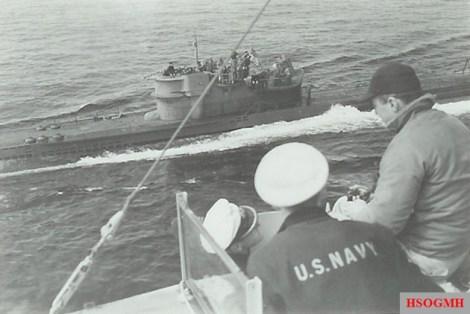 U-234 surrendering. Crewmen of Sutton (DE-771) in foreground with Kptlt. Johann-Heinrich Fehler (left-hand white cap).