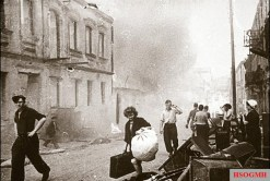 Civilians carry belongings out of burning houses, early July 1944.