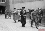 Karl Dönitz (centre, in long, dark coat) followed by Albert Speer (bareheaded) and Alfred Jodl (on Speer's right) during the arrest of the Flensburg government by British troops.