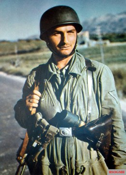 A German Fallschirmjäger (Paratrooper) with the rank of Gefreiter (Corporal) in his light olive green jump smock of the early version, armed to the teeth, during Unternehmen Merkur (Operation Mercury), German invasion of the Crete Island in Greece, May 1941.
