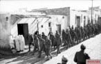 U.S. troops taken prisoner during the battle march through a Tunisian village.