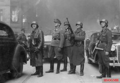 "Stroop Report original caption: ""The leader of the grand operation."" SS-Brigadeführer Jürgen Stroop (center) watches housing blocks burn."