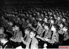 "Hitlerjugend demonstration under the banner of ""Die Ritterkreuzträger der Kriegsmarine Rede an die Hitlerjugend"" (The Knight's Cross Recipients of the German Navy Speech to the Hitler Youth) at the Berlin Sportpalast, 16 June 1943. Young Hitlerjugend listen to the speech of Kapitänleutnant Reinhard Hardegen (Kommandant U-123)."