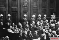 The Nuremberg defendants listen to the proceedings (Speer, top seated row, fifth from right).