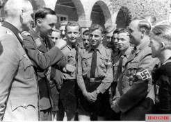 1 May 1943: Luftwaffe fighter ace and Ritterkreuzträger Hauptmann Adolf Dickfeld (second from left) tells the boys of Hitlerjugend about his experience as a combat pilot. Second from right is the leader of Hitlerjugend, Reichsjugendführer Artur Axmann. First from left is Sonderführer (Z) Kurt Leffler (Landwirtschaftsführer), the holder of Ritterkreuz des Kriegsverdienstkreuz mit Schwertern (Knight's Cross of the War Merit Cross with swords).