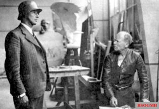 "Sculptor Arnold Waldschmidt (right) with a model for his stone relief ""Fahnenkompanie""."