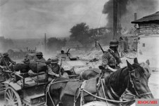 Wehrmacht horse drawn artillery and armored cars of the LSSAH pass a burning Soviet village August 1941.