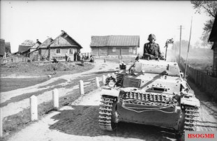 A Panzer II during Operation Barbarossa in 1941 moves along a road outside a village.