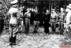 Award ceremony of 4. Panzer-Division, 12 August 1944. Divisionskommandeur Clemens Betzel (back to the camera) awarded the Ritterkreuz des Eisernen Kreuzes to Bataillonsführer Kurt Schäfer (on the right facing Betzel). From left to right: Oberst Hans Christern, Generalmajor Clemens Betzel, Oberstleutnant Gerlach von Gaudecker-Zuch, Oberstleutnant im Generalstab Peter Sauerbruch, Hauptmann Wilhelm Westermann, Major der Reserve Fritz-Rudolf Schultz, unidentified officer, Hauptmann Kurt Schäfer, and another unidentified officer.