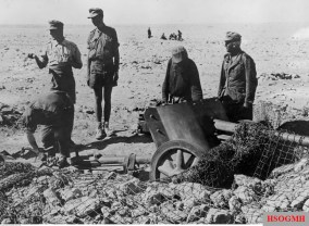 The working position of 5 cm Pak 38 (L/60) (5 cm Panzerabwehrkanone 38 (L/60)) at El Alamein positions, October 1942. Ritterkreuzträger Oberstleutnant Karl Ens (left) checks the camouflaged netting works.