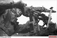 A young Fallschirmjäger checks his tripod-mounted MG 42.