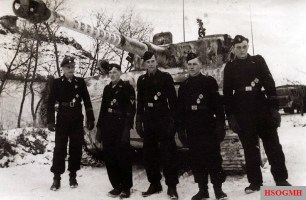 "This picture shows Wittmann with his crew, from left to right. SS-Panzerschütze Werner Irrgang (Funker), SS-Rottenführer Bobby Woll (Richtschütze), SS-Untersturmführer Michael Wittmann (Zugführer in 13.Kompanie (schwere) / IV.Abteilung / SS-Panzer-Regiment 1 / 1.SS-Panzer-Division ""Leibstandarte SS Adolf Hitler""), SS- Panzerschütze Sepp Rößner (Ladeschütze), and SS-Sturmmann Eugen Schmidt (Fahrer). Behind them is Wittmann's Panzerkampfwagen VI Tiger I Ausf.F S04, with 88 victory rings on its barrel. Actually the Ritterkreuz recommendation sent by Divisionskommandeur Wisch to the Oberkommando der Wehrmacht (OKW) on 10 January 1944 ""only"" included Wittmann's winnings as 66 tanks, but something incredible happens: in the four day span between the submission of the proposal to the official approval notification, this tank master went berserk and destroyed no fewer than 22 additional tanks to hoist his winning score to a total 88!"