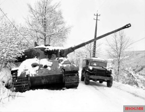 An American Dodge WC ambulance passes abandoned German Tiger II '204' from schwere SS-Panzer-Abteilung 501, Kampfgruppe Peiper, I. SS-Panzerkorps, near La Gleize, Belgium, December 1944. The vehicle was also laced with American graffiti.