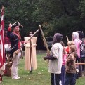 A Revolutionary War reenactment actor teaches children how to march at the Revolutionary Germantown Festival