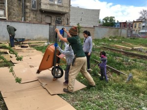 A woman and child tilt a wheelbarrow of mulch onto a path