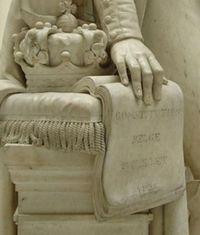 De hand van Koning Leopold rustend op de constitutie