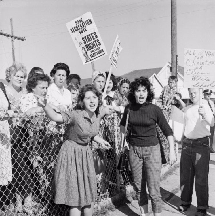 """Beroemde foto, gemaakt tijdens een van de protesten. Rechts houdt een protestant een bord omhoog met daarop de tekst """"Al I want for Christmas is a clean white school"""" (reddit)"""