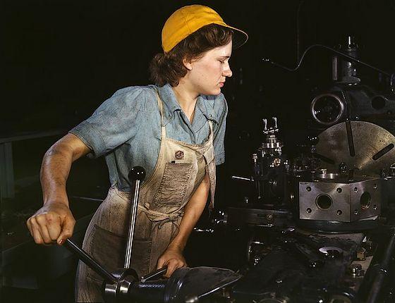 Een levende 'Rosie the Riveter' aan het werk in een fabriek – Foto: Hollem, Howard R.
