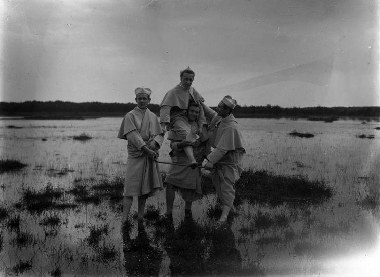 Waarschijnlijk gemaakt tussen 1920 en 1924. Vier jonge norbertijnen buiten de abdij, wadend door het water. - Foto: BHIC