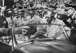 Adolf Hitler in een Volkswagen Kever cabriolet na de eerste steenlegging van de fabriek in 1938 met Jakob Werlin (rechts) en Ferdinand Porsche (tweede van rechts).
