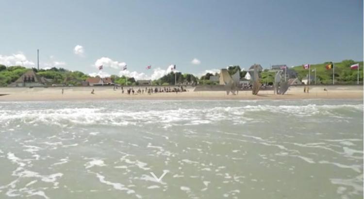 De website van 6 juni begint met beelden van het Normandisch strandvermaak in 2014 en gaat over naar dezelfde positie in 1944, als soldaten hun landingsvaartuig verlaten, op weg naar het Duitse spervuur op de kust. (Illustratiemateriaal website 'Op weg naar de bevrijding')