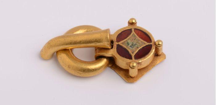 Gesp (goud, parel en granaat, datering 5de eeuw na Chr., hoogte 5.3cm; gevonden in Carthago) Collectie: Musée national de Carthage, Tunesië