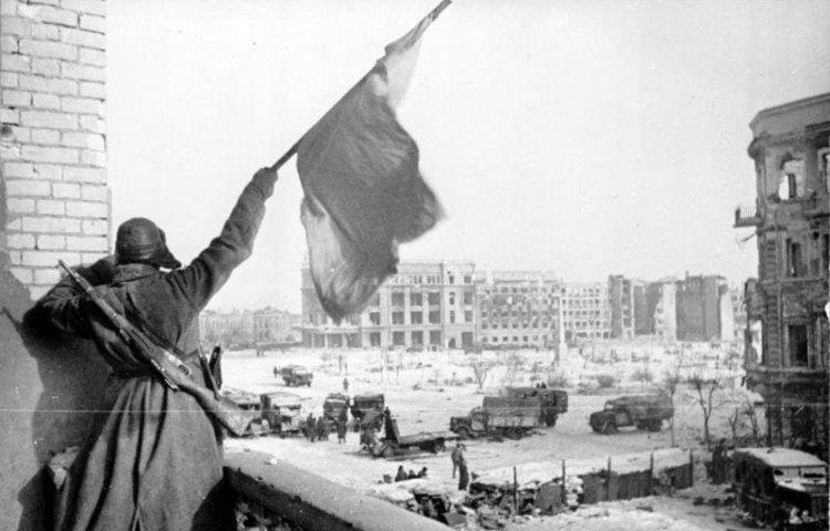 Sovjet-soldaat wappert met een vlag voor de overwinning om Stalingrad op 2 februari 1943
