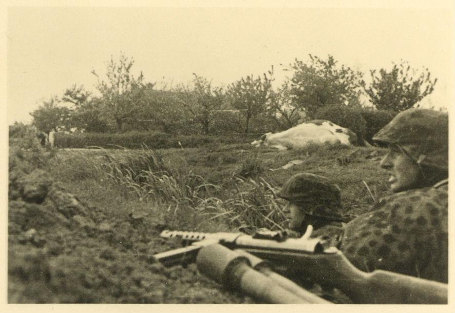 In de omgeving van de Haarweg liggen Duitse militairen in een greppel of slootbedding. De foto is genomen op 11 mei, toen er zwaar werd gevochten om de voorpostenstrook. In het veld ligt rechts een dodelijk getroffen koe en op de achtergrond zijn een boerderij en een boomgaard te zien. Gezien de vers omgewoelde grond links op de foto hebben de SS'ers zich met hun pioniersschoppen extra diep ingegraven. Op de voorgrond liggen twee steelhandgranaten klaar voor gebruik. Foto: Collectie Joost Bruinsma, Soest