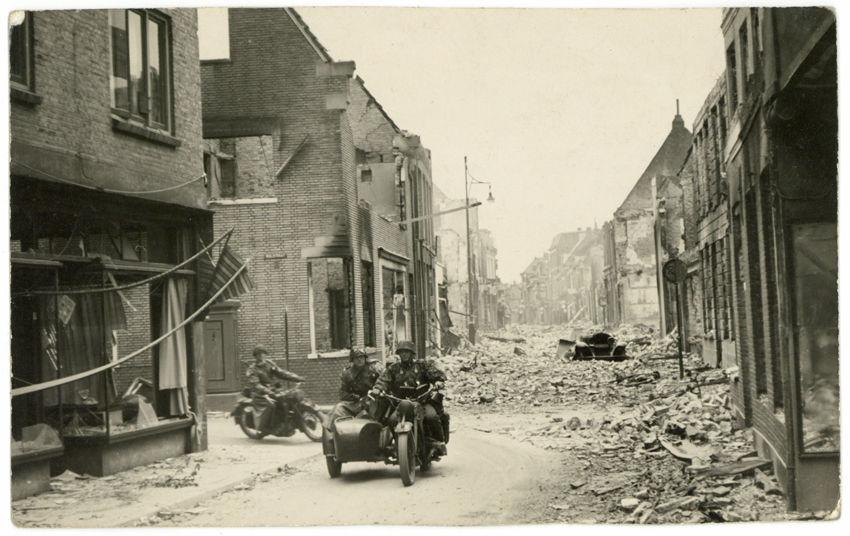 Op 13 of 14 mei draaien twee Duitse motoren vanuit de Walstraat de Wageningse Hoogstraat in. De Nederlandse artilleriebeschietingen hebben veel schade aangericht en grote delen van de Hoogstraat liggen in puin. Te midden van de brokstukken is een Duits militair autowrak te zien, dat door een ingestorte gevel is bedolven. De Duitse motorrijders hebben op weg naar de Grebbeberg moeten omrijden omdat de hoofdroute door de Hoogstraat geheel versperd is. Ze zijn als SS'ers te herkennen aan hun camouflagepakken. - Foto: Collectie Joost Bruinsma, Soest