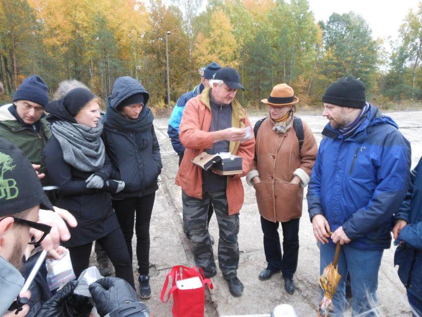 Archeoloog Wojtek Mazurek toont enkele artefacten aan de deelnemers