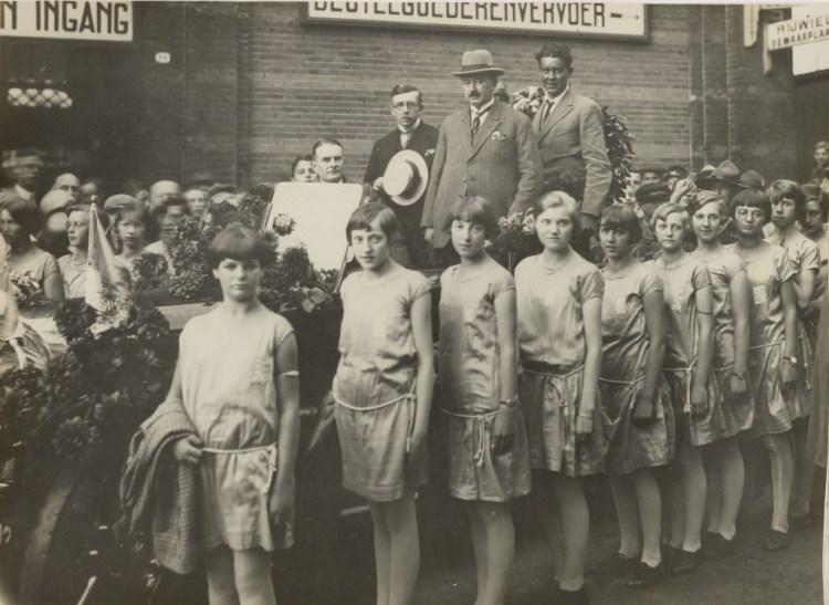 Tienduizenden mensen juichen Sjef van Dongen toe tijdens zijn rijtoer en huldiging in Arnhem. Naast de auto liep een escorte van vrouwelijke leden van sportvereniging U.D.I., oftewel Uitspanning Door Inspanning. (Zeeuws Archief)